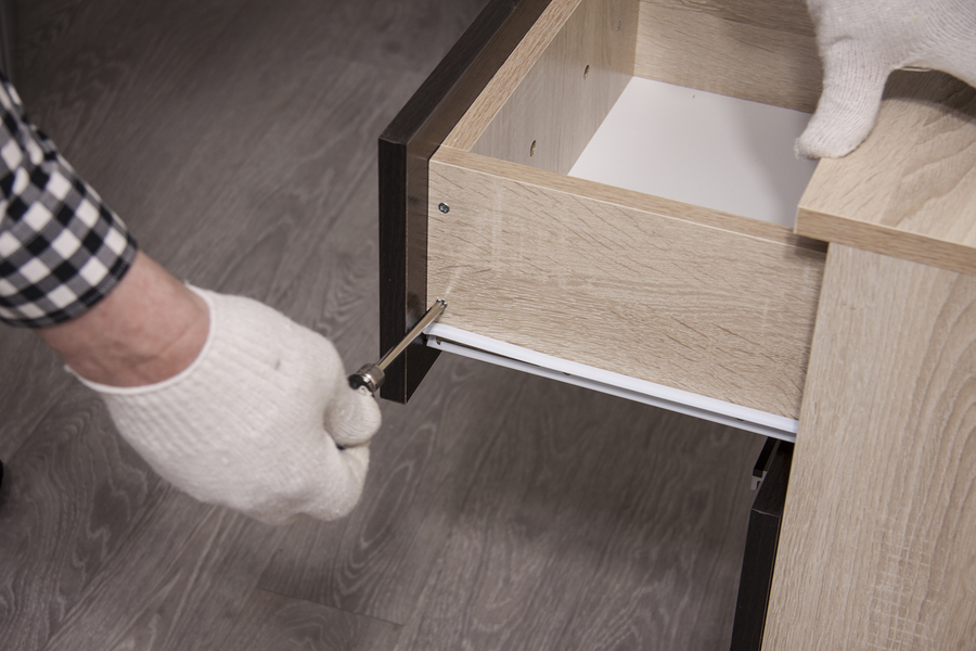 professional furniture expert repairing cabinets